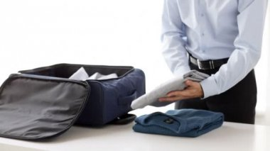 Businessman packing clothes into travel bag — Stock Video