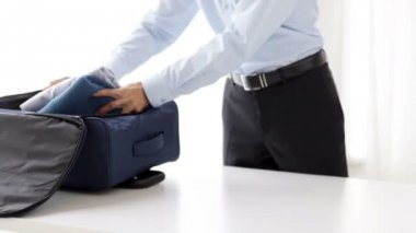 Businessman packing clothes into travel bag — Stockvideo