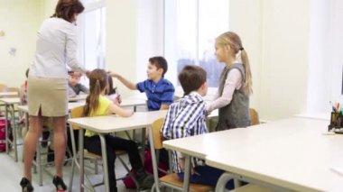 Lehrer Schulkinder im Klassenzimmer Stifte einzuräumen — Stockvideo