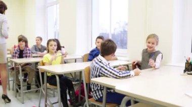 Teacher giving pens to school kids in classroom — Stock Video