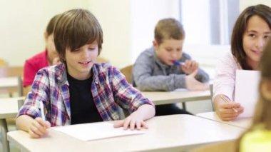 Groupe d'écoliers écrivant test en salle de classe — Vidéo