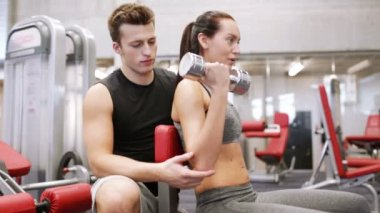 Young couple with dumbbell flexing muscles in gym — Vídeo de Stock