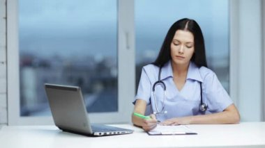 Doctor or nurse with laptop pc writing prescription — Video Stock