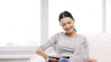 Souriant magazine de lecture femme à la maison — Vidéo