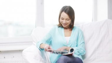 Smiling woman reading magazine and sitting on couch — 图库视频影像