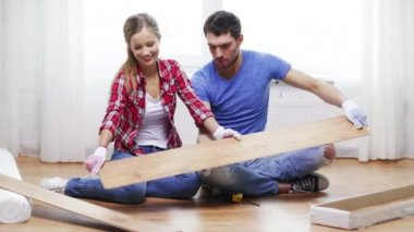 Couple taking out wood flooring from package — Stock Video