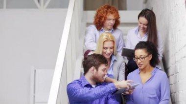 Команда с планшетного компьютера pc, сидя на лестнице — Стоковое видео
