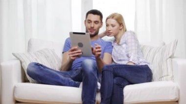 Sonriente pareja feliz con tablet pc en casa — Vídeo de Stock