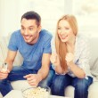Smiling couple with popcorn cheering sports team — Stock Photo #60816315