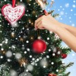 Close up of hands with christmas tree decoration — Stock Photo #60816685
