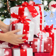 Close up of woman with gifts and christmas tree — Stock Photo #60816715