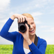 Smiling woman taking picture with digital camera — Stock Photo #60818229