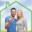 Smiling couple holding key over green house — Stock Photo #60818743