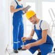 Builders with tablet pc and equipment indoors — Stock Photo #60818989