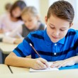 Group of school kids writing test in classroom — Stock Photo #60819109