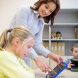 Little girl with teacher and tablet pc at school — Stock Photo #60819255
