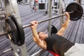 若い男がジムでバーベルで筋肉を屈曲 — ストック写真