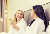 Smiling girlfriends with champagne glasses in bed — Stock Photo