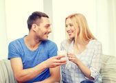Uomo sorridente dando una tazza di tè o caffè alla moglie — Foto Stock