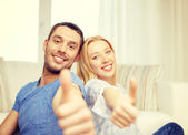 Smiling happy couple at home showing thumbs up — Stock Photo