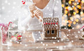 Close up of woman making gingerbread house at home — Stock Photo