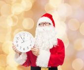 Man in costume of santa claus with clock — Stock Photo