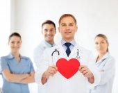 Doctor hombre sonriente con corazón rojo y un estetoscopio — Foto de Stock