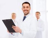 Doctor hombre sonriente con portapapeles — Foto de Stock
