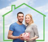 Smiling couple holding piggy bank over green house — Stock Photo