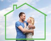 Улыбчивая пара, обнимающая по зеленому дому — Стоковое фото