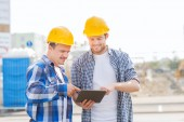 Smiling builders in hardhats with tablet pc — Stock fotografie