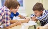 Group of schoolboys writing or drawing at school — Stock Photo