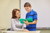 School boy with notebook and teacher in classroom — Stockfoto