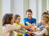 Group of smiling school kids putting hands on top — Stock Photo
