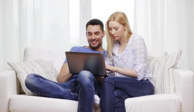 Smiling couple with laptop computer at home — Stock Video