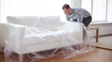 Male putting down new sofa at home — Vídeo de stock