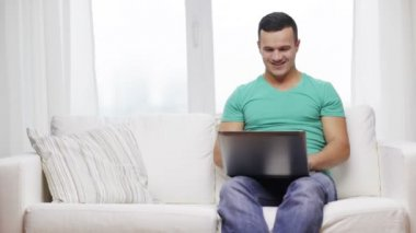 Smiling man working with laptop at home — Stock Video