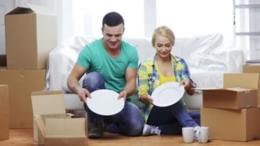 Smiling couple unpacking boxes with kitchenware — Stock Video