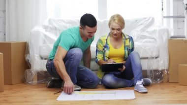 Smiling couple looking at blueprint in new home — Stock Video