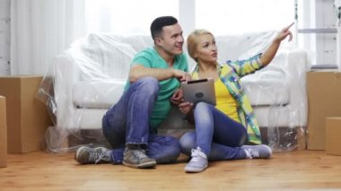 Smiling couple with tablet pc in new home — Stock Video