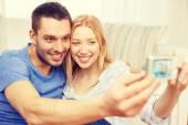Uśmiechnięta para biorąc obraz z aparatu cyfrowego — Zdjęcie stockowe