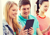 Smiling students with tablet pc at school — Stockfoto