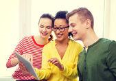 Lachende studenten met de tablet pc op school — Stockfoto