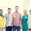 Happy creative team showing thumbs up in office — Stock Photo #60851391