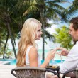 Couple drinking wine in cafe on hotel beach — Stock Photo #60853259