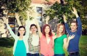Grupa studentów uśmiechający się, machanie rękami — Zdjęcie stockowe