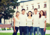 Group of smiling teenagers in white blank t-shirts — Stock Photo