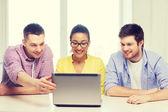 Tres colegas sonrientes con el portátil en la oficina — Foto de Stock