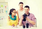 Equipo sonriente con cámaras trabajando en oficina — Foto de Stock