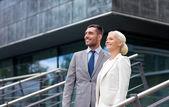 Empresarios sonrientes junto a edificio de oficinas — Foto de Stock